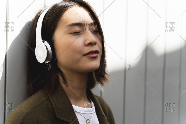 Relaxed young woman with closed eyes listening to music with headphones