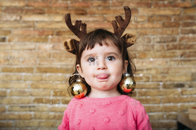 Portrait of toddler girl sticking out tongue wearing reindeer antlers headband and Christmas baubles