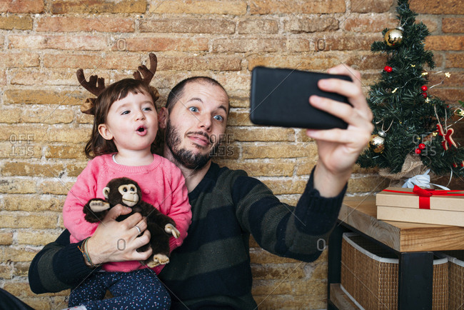 Portrait of father and little daughter taking selfie with smartphone at Christmas time