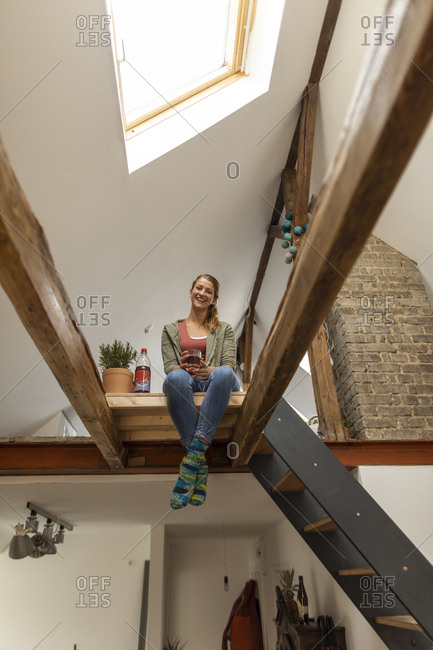 Smiling young woman sitting on attic
