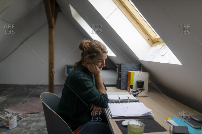 Young woman sitting at desk in attic studying folder