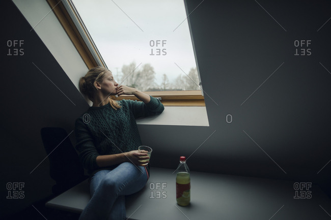 Young woman looking out of attic window