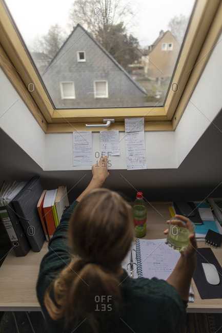 Rear view of young woman sitting at desk in attic learning