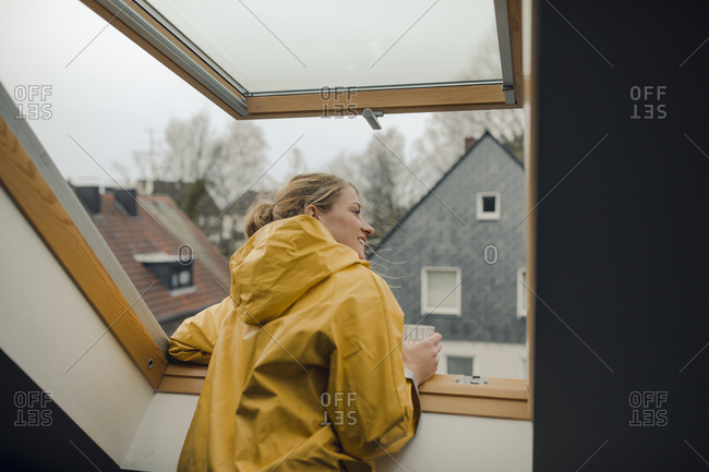Smiling young woman in raincoat looking out of attic window