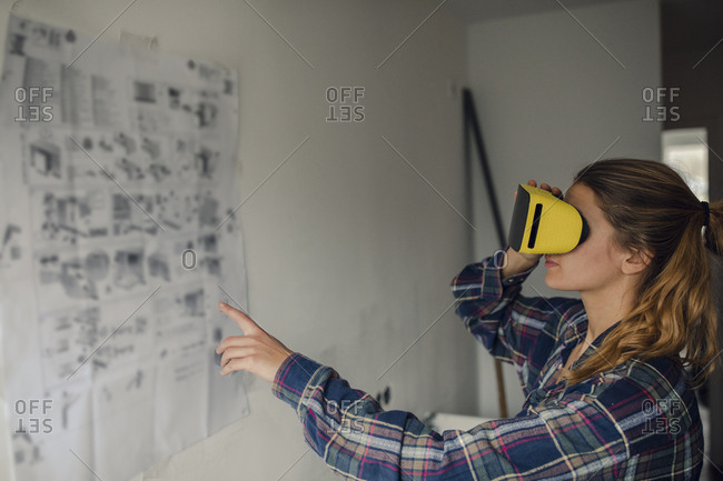 Young woman wearing VR glasses with assembly instructions at the wall