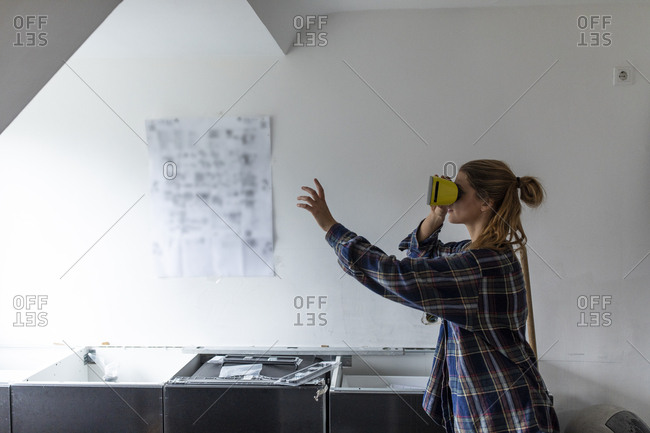 Young woman wearing VR glasses with assembly instructions at kitchen wall