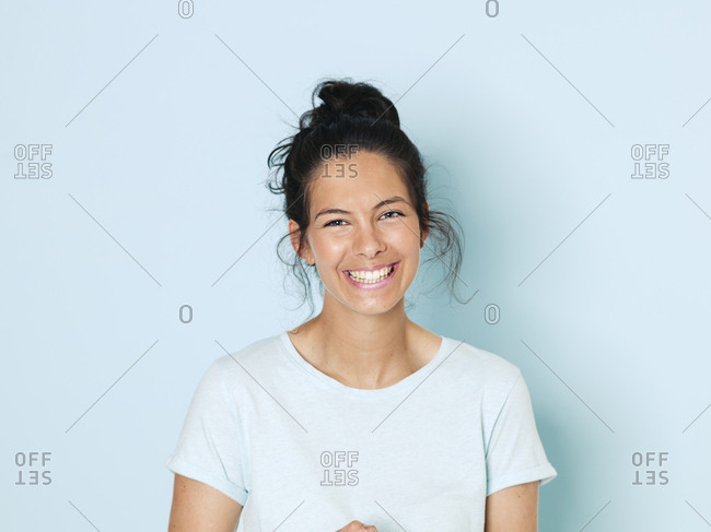 Portrait of young woman with black hair- light blue background