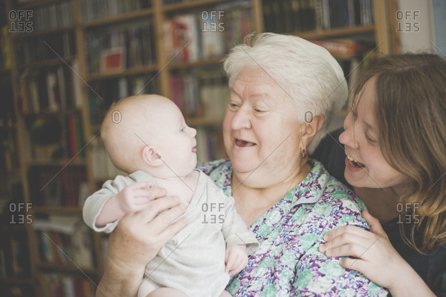 Happy grandmother with mother holding a baby girl