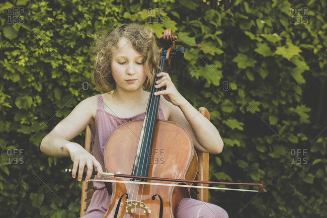 A girl playing the cello in garden
