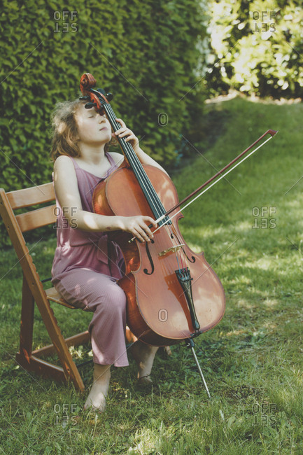 A girl playing the cello  with eyes closed in garden