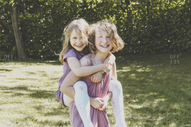 A big sister carrying her small sister- Girl power