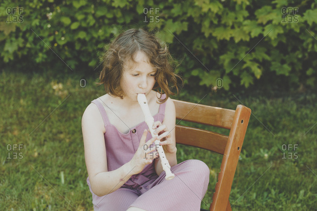 A girl playing the flute in the garden