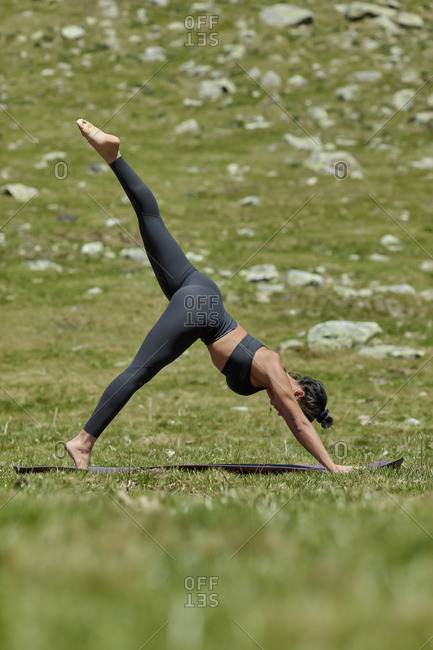 Young woman doing yoga on meadow- downward facing dog position