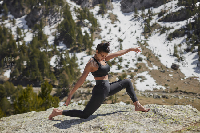 Young woman doing yoga in nature- warrior pose on rock