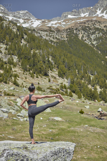 Young woman doing yoga in nature- standing on one leg- Hasta Padangustasana