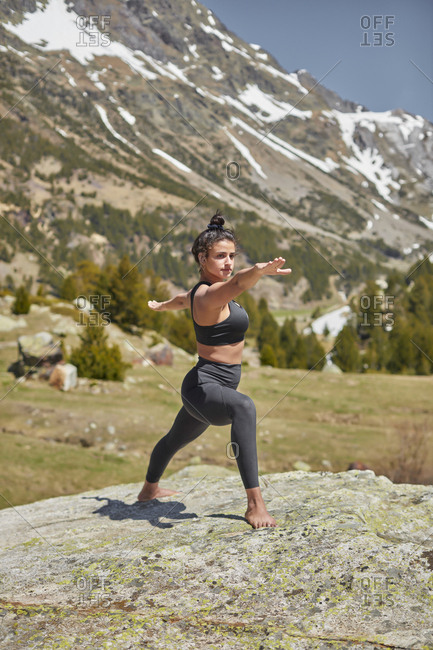 Young woman doing yoga  standing on rock in nature- warrior pose