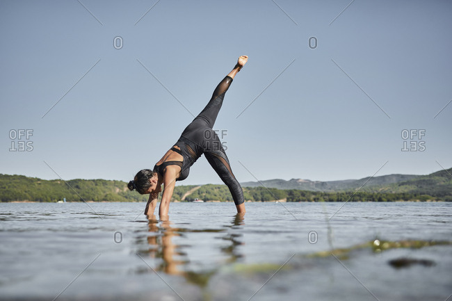 Young woman doing yoga in nature- downward facing dog pose