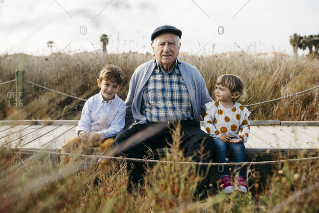 Portrait of grandfather sitting with his grandchildren side by side on boardwalk