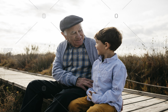 Happy grandfather sitting with his grandson on boardwalk looking at each other