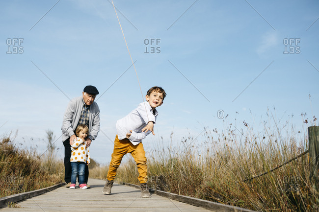 Boy on boardwalk throwing stick while his grandfather and his little sister watching him from the background