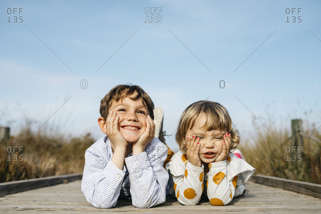 Portrait of boy and his little sister lying side by side on boardwalk pulling funny faces