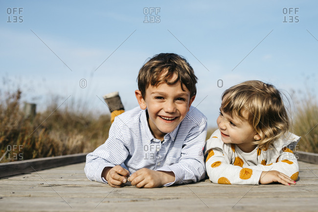Portrait of boy and his little sister lying side by side on boardwalk having fun