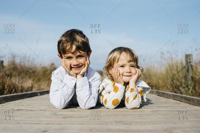 Portrait of boy and his little sister lying side by side on boardwalk
