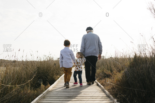 Back view of grandfather and grandchildren strolling hand in hand on boardwalk