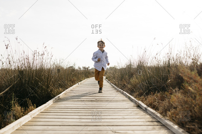 Happy little boy running on boardwalk