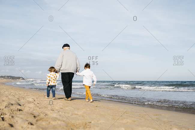 Back view of grandfather strolling with his grandchildren hand in hand on the beach