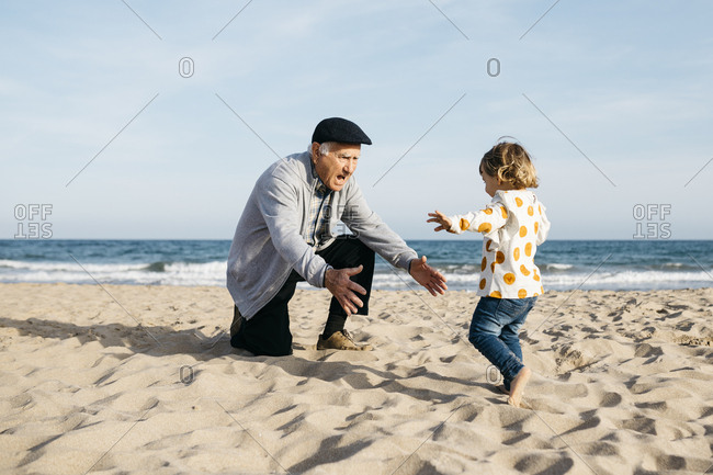 Grandfather playing with his little granddaughter on the beach