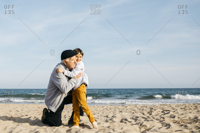 Grandfather and grandson hugging on the beach