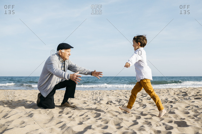 Grandfather playing with his grandson on the beach