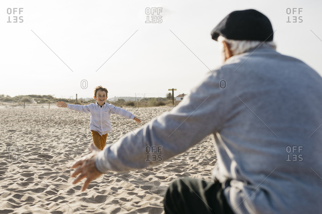 Happy little boy running into his grandfather's arms on the beach