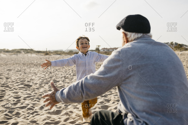 Portrait of happy little boy running into his grandfather's arms on the beach