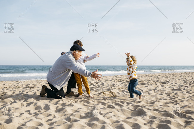 Grandfather playing with his grandchildren on the beach in spring