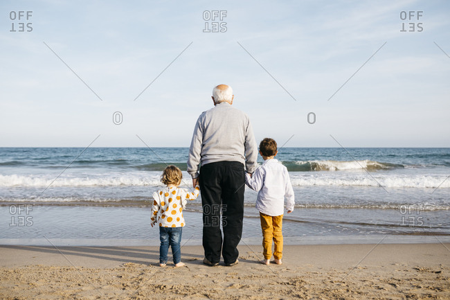 Back view of grandfather standing hand in hand on the beach with his grandchildren watching the sea