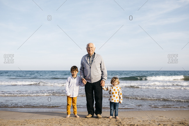 Portrait of happy grandfather standing hand in hand on the beach with his grandchildren
