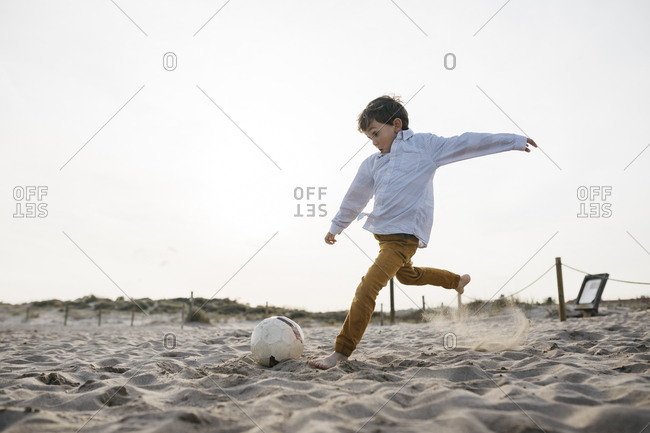 Little boy playing soccer on the beach kicking the ball