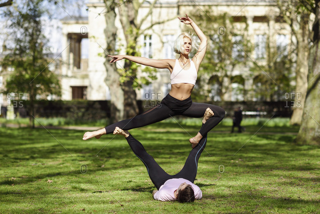 Young couple doing yoga acrobatics in an urban park