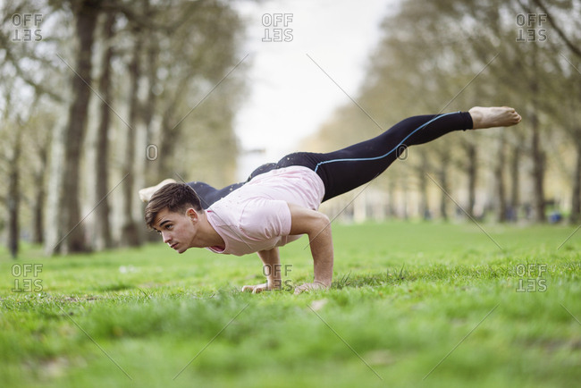 Young man doing gymnastic acrobatics in an urban park