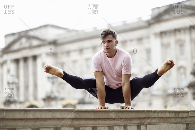 UK- London- young man doing gymnastic acrobatics in front of Buckingham Palace