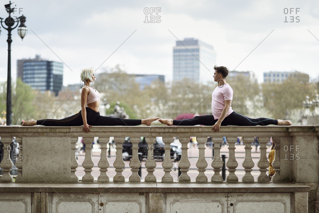 UK- London- young couple doing gymnastic acrobatics on parapet at Buckingham Palace