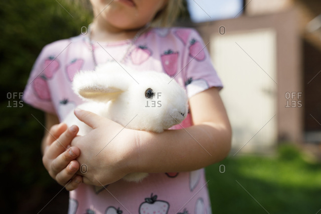 Close-up of girl holding toy bunny outdoors