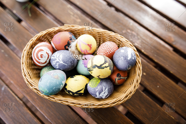 Easter eggs in basket on wooden table