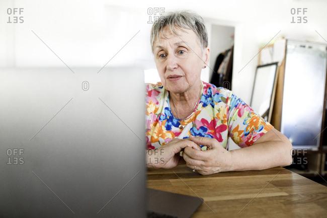 Senior woman sitting at table at home using laptop