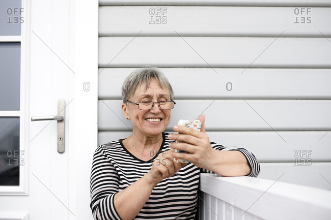 Happy senior woman using cell phone on porch of her house