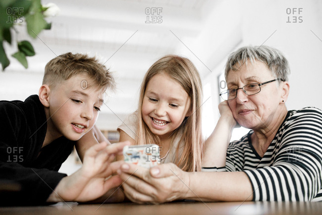 Happy grandmother and grandchildren using  cell phone at home