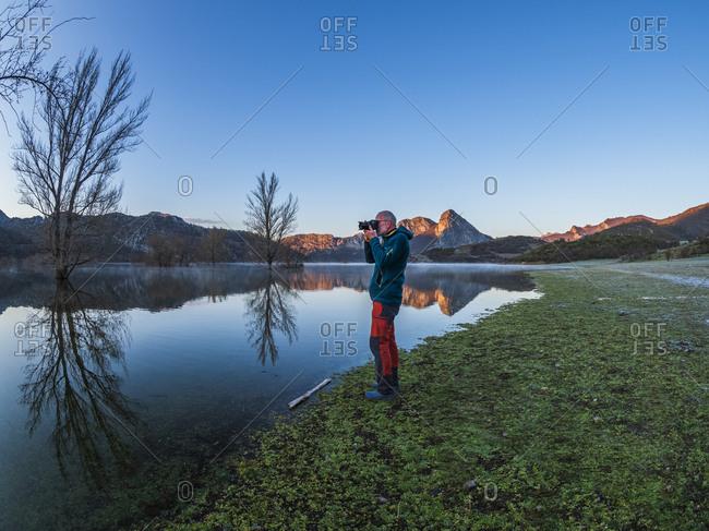 Spain- Asturias- Camposolillo- Cantabrian Mountains- senior man taking a photo at the seashore of Porma reservoir