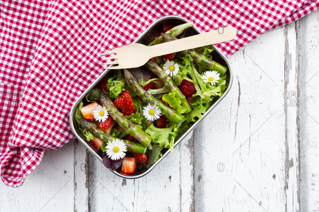 Lunchbox with green salad- green asparagus- strawberries and daisies